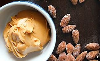 Almond butter in dish beside raw almonds