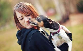 Dog licking woman's face