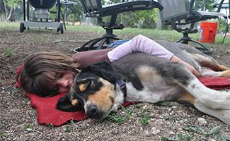 Girl hugging dog on the ground