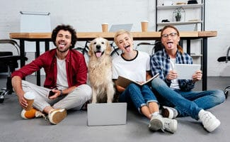 Three business colleagues and a dog sitting in front of a wooden conference table with their tongues out