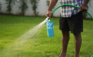 Man spraying Sunday Lawn Care on grass with hose